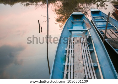 spoon net and little paddle in blue boat in evening time #1050301139
