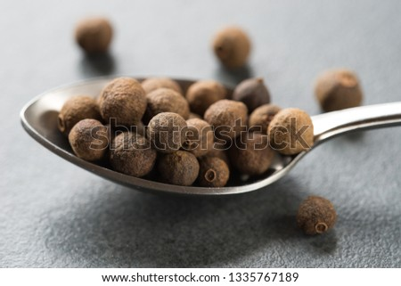 spoon of allspice seeds on table macro #1335767189