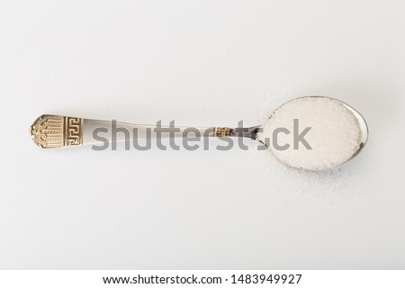 Spoon of fine granulated sugar isolated on white