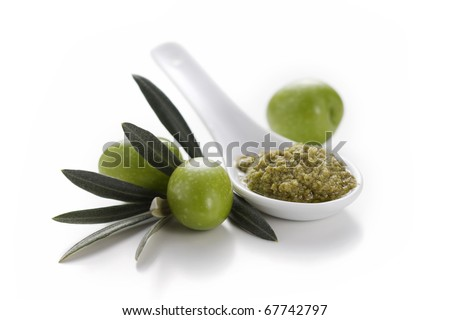 Spoon of green olive pate with olives and leaves on white background
