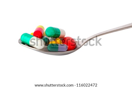 Spoon of pills isolated on white
