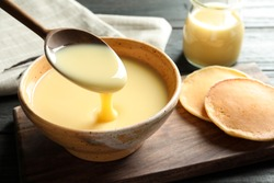 Spoon of pouring condensed milk over bowl on table, space for text. Dairy products