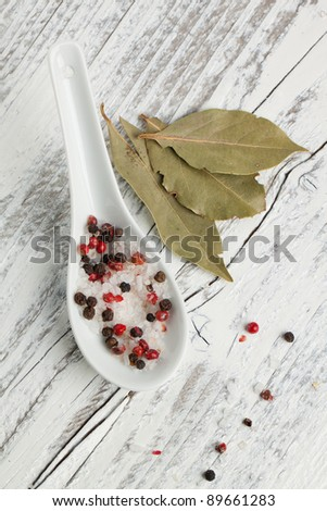 Spoon of salt and pepper with bay-leaf on white wooden table