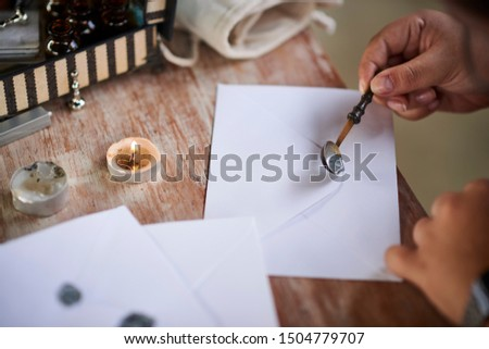 Spoon of wax, gray sealing and white envelope. Woman seals on a letter on a wooden table