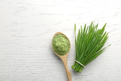 Spoon of wheat grass powder and green sprouts on white wooden table, flat lay. Space for text