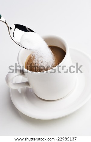 Spoon pouring sugar into a cup of coffee
