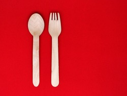 Spoon set with wood drills on red background.