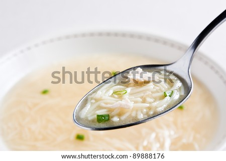 Spoon soup with noodles and soup in the blurred background
