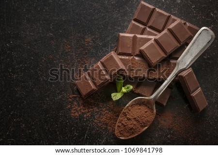 Spoon with cocoa powder and tasty chocolate on dark background, top view