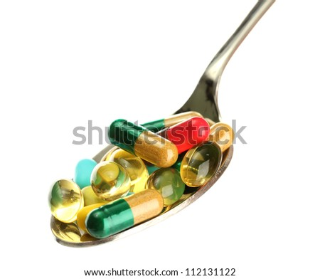 spoon with colorful capsules and pills, isolated on white