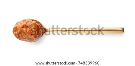 Spoon with delicious caramel sauce on white background #748339960