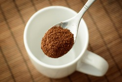 Spoon with ground coffee over the white empty cup against a brown bamboo background. Making coffee