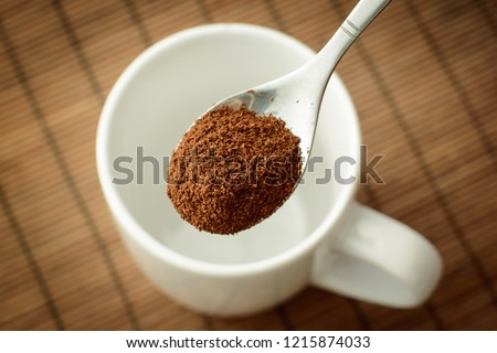 Spoon with ground coffee over the white empty cup against a brown bamboo background. Making coffee #1215874033