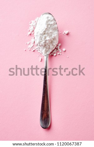 Spoon with powder sugar isolated on pink background, top view