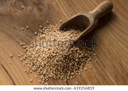 spoon with sesame seeds  on wooden table