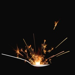 Spoon with sparkler isolated on dark background. Flavor and taste explosion.