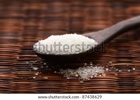 spoon with sugar closeup on wooden background