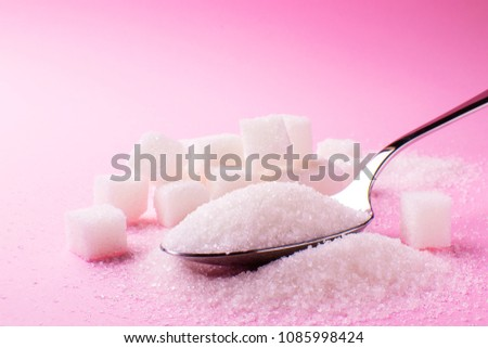 spoon with sugar on a pink background, side view