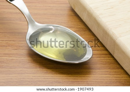 Spoonful of cooking oil besides a chopping board
