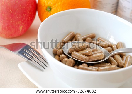 Spoonful of medicine capsules in soup bowl with fruits in background. Signifying drug addiction, healthy eating and lifestyle, dieting and slimming, and healthcare concepts.