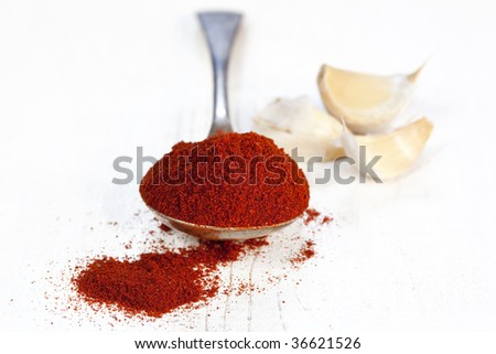 Spoonful of paprika, with cloves of garlic.  Very shallow DOF.  Perfect for a traditional Hungarian goulash.