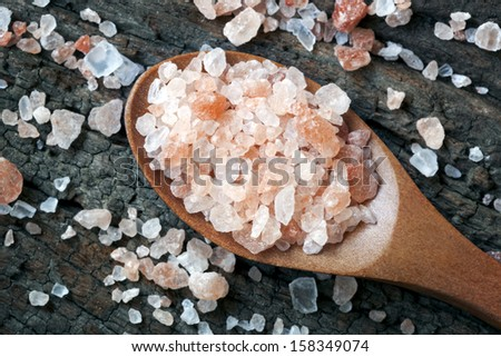 Spoonful of pink Himalayan rock salt, over weathered timber.