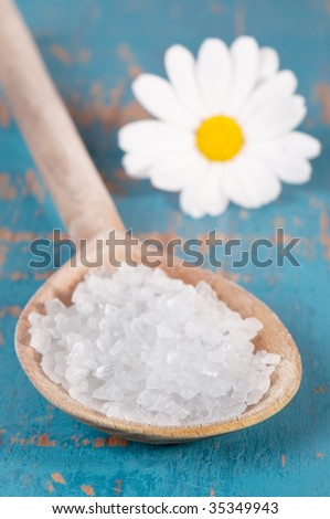 Spoonful of sea salt crystals on wooden spoon with daisy in background