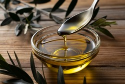 Spooning olive oil into a bowl placed on a wooden background