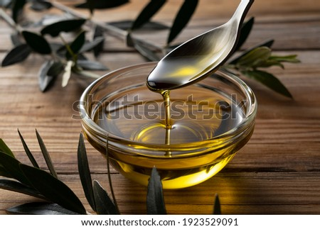 Spooning olive oil into a bowl placed on a wooden background Stock fotó ©
