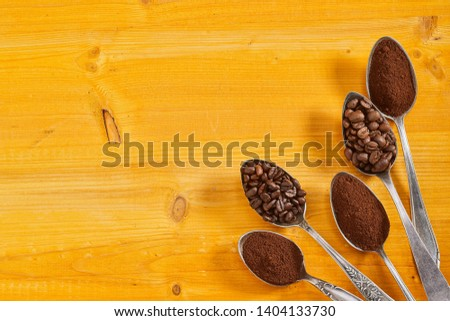 Spoons displaying fresh ground coffee and medium and full roasted beans arranged from the corner on colorful yellow stained wood with copy space #1404133730