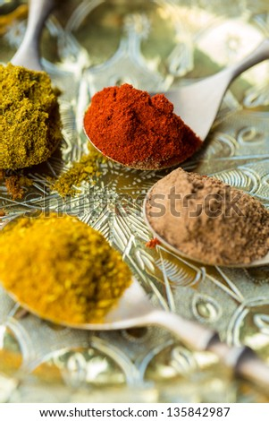 Spoons of curry powder, allspice, paprika