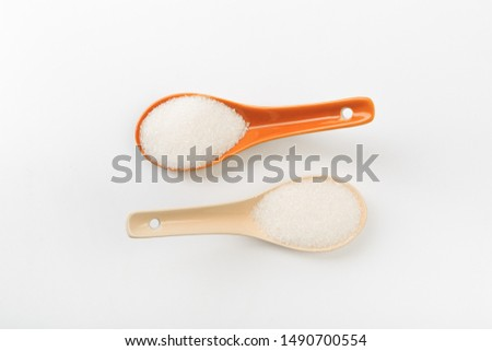 Spoons  of fine granulated sugar isolated on white