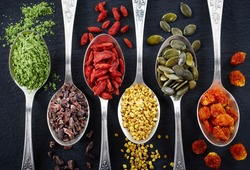 Spoons of various superfoods on black background