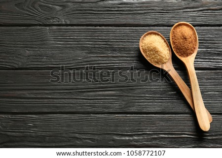 Spoons with brown sugar on wooden table