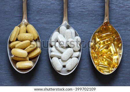 Spoons with healthy supplements on a dark stone background