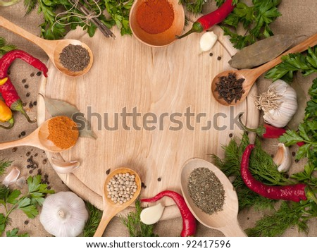 spoons with spices on wooden board background