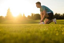 Sporsmen preparing to run. Athlete preparing for cross-country. Morning running. Guy tying shoelaces on sneakers.