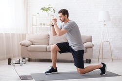 Sport activities at home. Young man watches online exercises and doing lunges in bright living room interior
