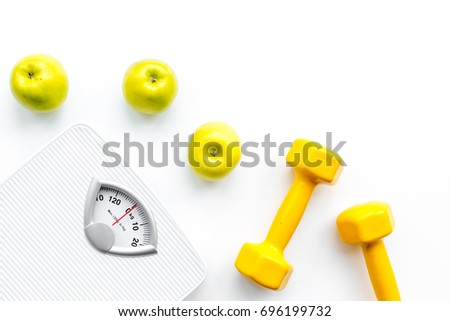 Sport and diet for losing weight. Bathroom scale, apple and dumbbell on white background top view copyspace