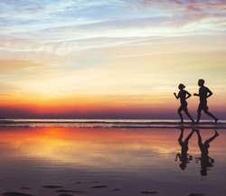 sport and health, two runners on the beach, silhouette of people jogging at sunset, man and woman healthy lifestyle background