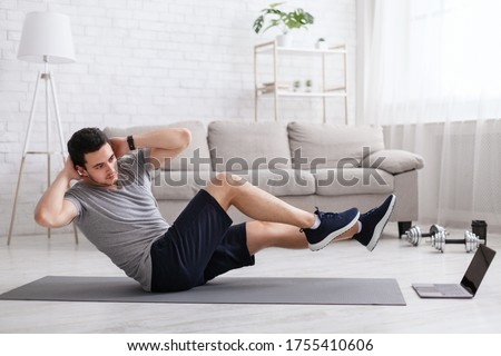 Sport and healthy lifestyle. Man put hands behind his head and does exercises for abdominal muscles and watch online training at home in interior