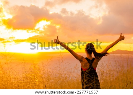 Sport and life achievements and success concept.. Sporty girl raising arms towards beautiful glowing sunshine.