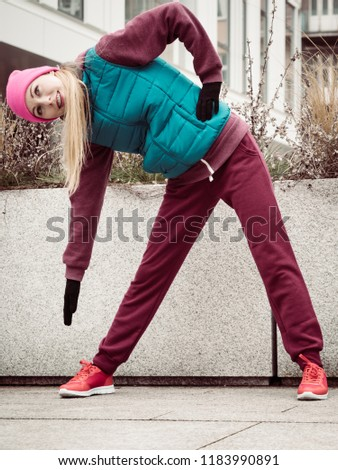 Sport and recreation. Fit slim sporty teen girl stretching warming up outdoor on city street. Woman exercising on fresh air. #1183990891