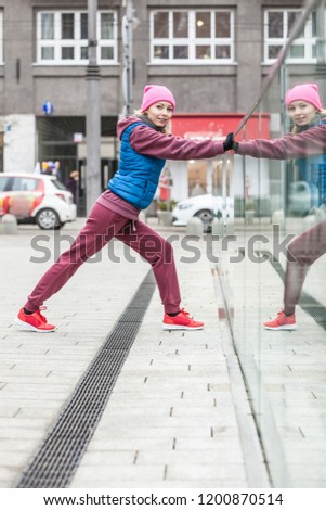 Sport and recreation. Fit slim sporty teen girl stretching warming up outdoor on city street. Woman exercising on fresh air. #1200870514