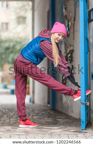 Sport and recreation. Fit slim sporty teen girl stretching warming up outdoor on city street. Woman exercising on fresh air. #1202246566