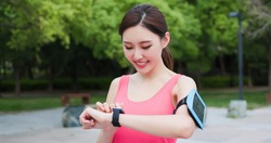 sport asia woman use wearable fitness tracker smart watch and running with smartphone in the park
