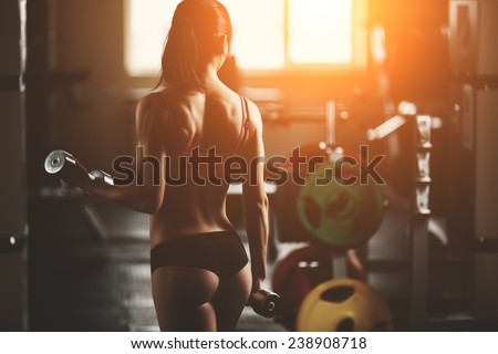 Stock Photo Sport. Athletic fitness woman pumping up muscles with dumbbells. Brunette sexy fitness girl in pink sport wear with perfect body in the gym posing before training set. Fitness woman in the gym.