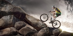 Sport background. Cyclist climbing on a rock.