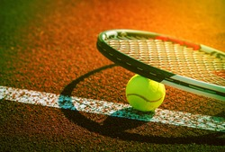 Sport background design dark tone. Closeup tennis ball and racket on line point on clay court.