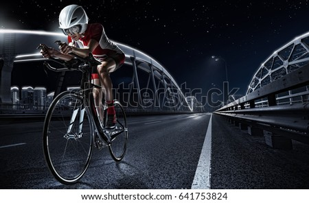 Sport backgrouns. Athletic woman cycling road bike in the evening. Dramatic view of the night city. #641753824